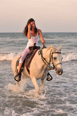 caballo de mar: caballo de lwhite de beautifu en el mar y la hermosa mujer  Foto de archivo