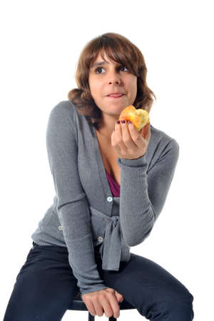 beautiful teenager eating an apple in front of a white background photo
