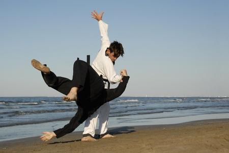 arte marcial: combates de dos hombres en los deportes de taekwondo y apkido en la playa Foto de archivo
