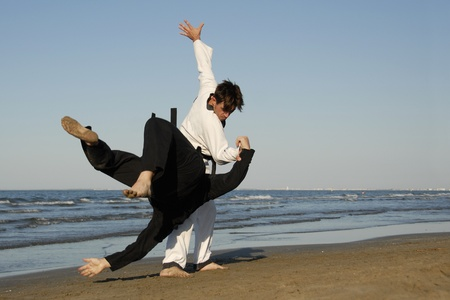 combative: fighting of two men in taekwondo and apkido sports on the beach