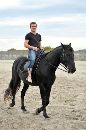 caballo de mar: joven y su semental negro en la playa