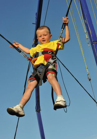 bungee jumping: Ni�o peque�o saltando en la cama el�stica (bungee jumping).