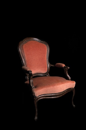 antique red armchair on a black background photo