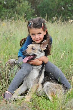 little girl and her baby purebred wolf dog photo