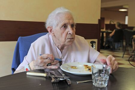 alimentation: senior woman smiling and eating in a  retirement facility Stock Photo