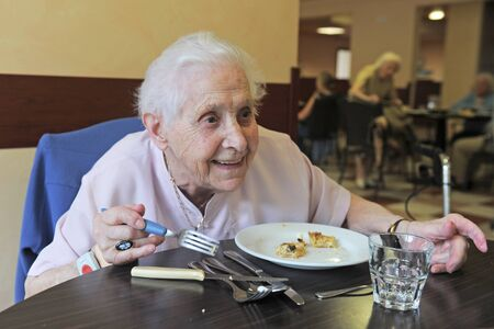 senior woman smiling and eating in a  retirement facility photo