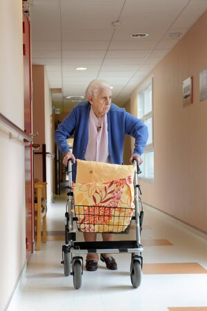 senior woman pushing a walking frame in a  retirement facility photo