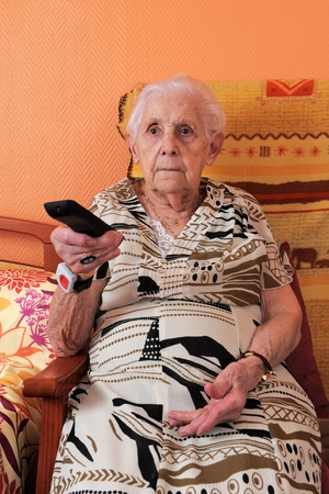 independance: Senior woman changing the TV channel with a remote control