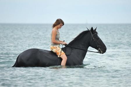 beautiful black  horse in the sea and beautiful woman photo