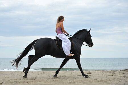 beautiful black  horse on the beach and beautiful woman photo