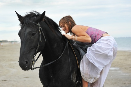 beautiful black  horse on the beach and beautiful woman mount it  photo