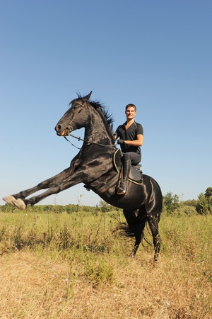 young man and his beautiful black stallion rearing up photo