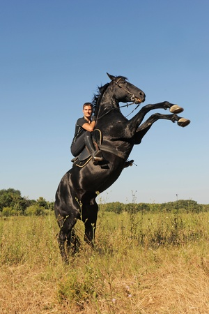young man and her beautiful black stallion rearing up Stock Photo - 9998826