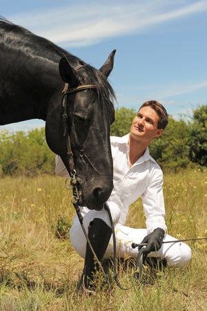 black horses: young man and his black stallion in  a field