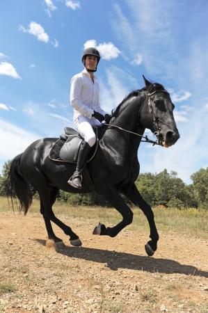 uomo a cavallo: giovane uomo e suo stallone nero in un campo