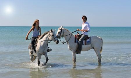 mann mit langen haaren: Vater und Tochter mit arabischen und Camargue-Pferde im Meer mit einer Abendsonne Lizenzfreie Bilder