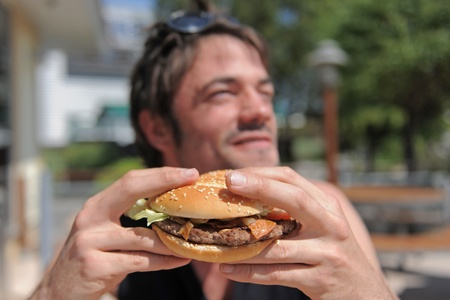 sandwitch: a man eating a hamburger in a fastfood, focus on the sandwitch