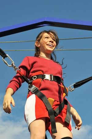 bungee jumping: adolescente sonriente en la cama elástica (bungee jumping). Foto de archivo