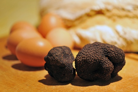 truffle: black truffles (tuber melanosporum) on a table with eggs and bred