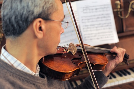 piano player: violinist with piano in the background, focus on the violin