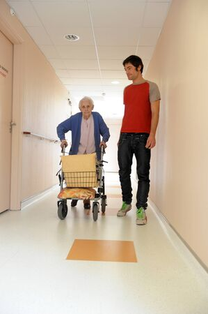 80 plus years: senior woman pushing a walking frame in a  retirement facility