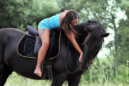 young teenager stroking her black stallion in a field photo
