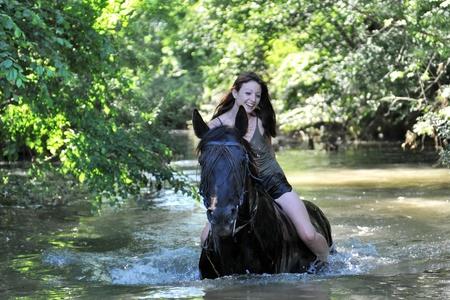 caballo de mar: hermoso caballo negro en el mar y la mujer hermosa Foto de archivo