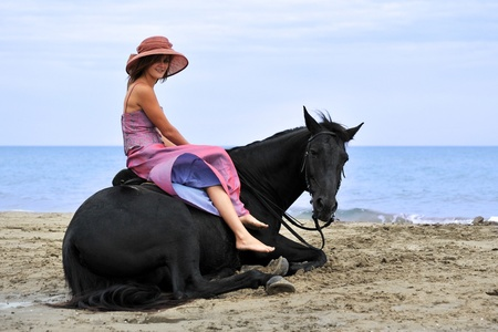beautiful black horse laid down on the beach and young woman photo
