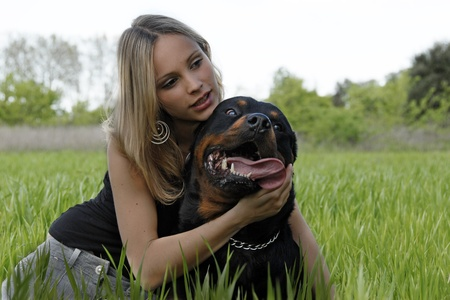 portrait of a purebred rottweiler and young woman photo