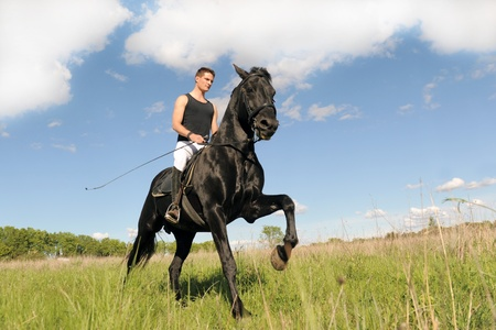 galloping: young man and his black stallion in  a field