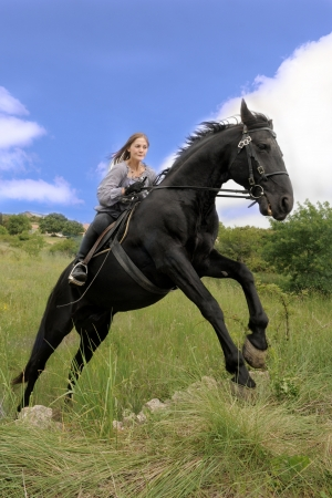 rearing: young woman and her black stallion in a field