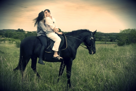 women kissing: beautiful black stallion in a field with young couple, vintage effect Stock Photo