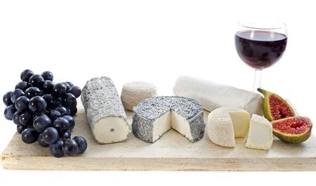 queso de cabra: diversos tipos de queso de cabra local, especialidad, fruta y un vaso de vino delante de fondo blanco Foto de archivo