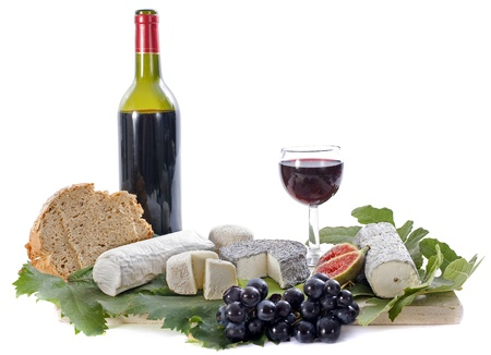 various of local speciality goat cheese, fruits and wine in front of white background photo