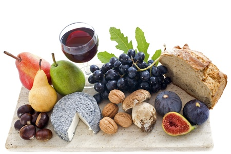 grapes and mushrooms: local speciality goat cheese, fruits and glass of wine in front of white background