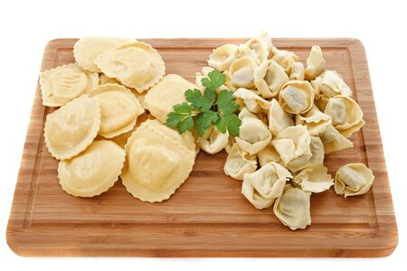 two varieties of raviolis on a cutting board in front of white background photo