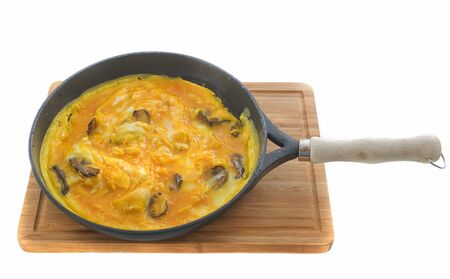 breakfeast: mushrooms omelet on a cutting board in front of white background Stock Photo