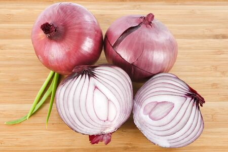 red onion on a wood cutting board photo