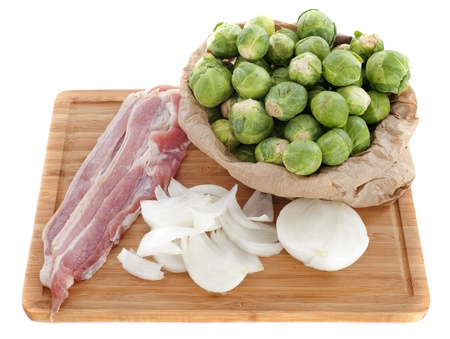 Brussels sprouts, onions, and raw bacon in front of white background Stock Photo - 16898099