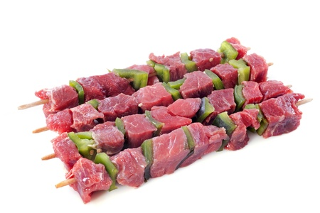 skewers of beef in front of white background