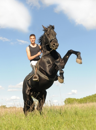 rearing: young man and her beautiful black stallion rearing up Stock Photo