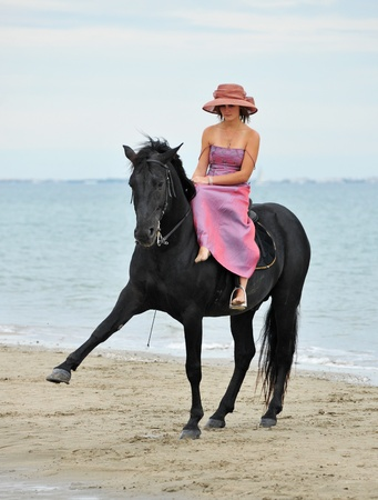 beautiful black stallion on the beach with young woman Stock Photo - 22111588