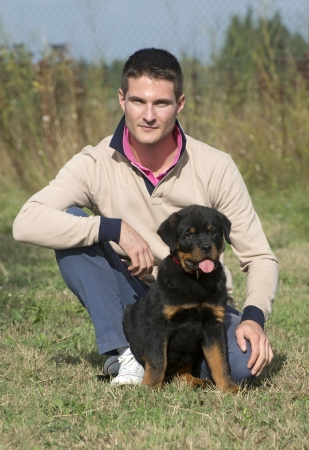 man and puppy rottweiler in a garden Stock Photo - 23648737