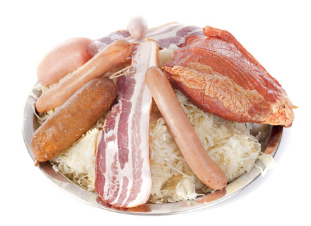 Sauerkraut and cooked meats in front of white background