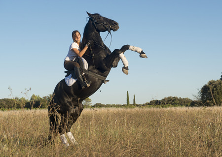 young girl riding a black stallion in the nature