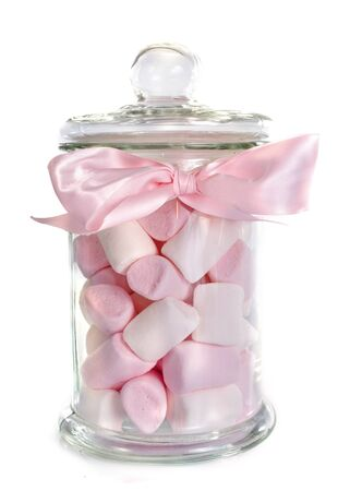 glass background: candy in bottle in front of white background