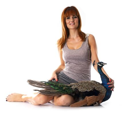 poultry: young woman and peacock in front of white background