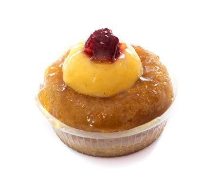 postres: ron torta baba delante de fondo blanco
