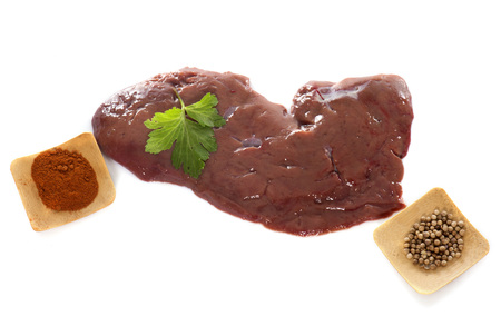 offal: calfs liver and parsley in front of white background