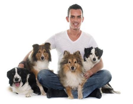 grupo de hombres: cuatro perros hermosas y hombre delante de fondo blanco